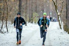 运行在雪的两个年轻运动员赛跑者落后森林 库存照片