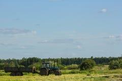 运行在领域的拖拉机反对蓝天背景 图库摄影