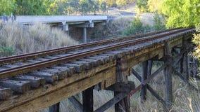 运行在高速公路附近的一座使用的铁路桥。 免版税库存图片