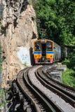 运行在死亡铁路轨道横穿kanchanaburi的泰国kwai河的火车 免版税库存图片