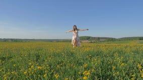 运行往与黄色花的一个领域和举胳膊的礼服的妇女 股票视频
