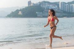 运行沿与明亮的阳光的海滩的比基尼泳装的运动的少妇和多山游览城市在背景中 免版税库存图片