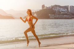 运行沿与明亮的阳光的海滩的比基尼泳装的运动的少妇和多山游览城市在背景中 免版税图库摄影