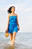 运行沿海浪拖鞋边缘的妇女  图库摄影