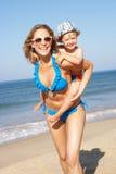 运行沿海滩的母亲和儿子 免版税库存照片