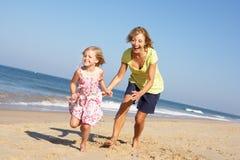 运行沿海滩的祖母和孙女 免版税库存照片