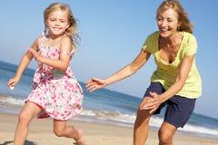 运行沿海滩的祖母和孙女 免版税库存图片