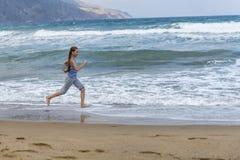 运行沿海滩的镶边T恤杉的女孩 库存图片