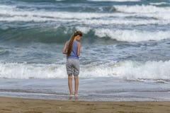 运行沿海滩的镶边T恤杉的女孩 免版税库存照片