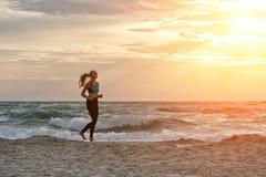 运行沿着海浪线的运动服的女孩 在美丽的鸟云彩之上颜色及早飞行金子早晨本质宜人的平静的反映上升海运一些星期日 库存图片