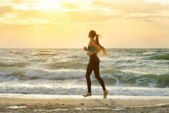 运行沿着海浪线的运动服的女孩 在美丽的鸟云彩之上颜色及早飞行金子早晨本质宜人的平静的反映上升海运一些星期日 免版税库存图片