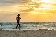 运行沿着海浪线的运动服的女孩 在美丽的鸟云彩之上颜色及早飞行金子早晨本质宜人的平静的反映上升海运一些星期日 图库摄影