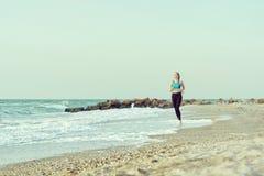 运行沿着海浪线的运动服的女孩 在美丽的鸟云彩之上颜色及早飞行金子早晨本质宜人的平静的反映上升海运一些星期日 免版税库存照片
