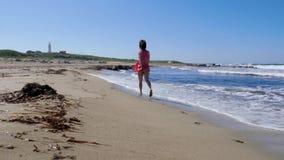 运行沿空的海滩的红色礼服的年轻女人 强的波浪飞溅并且包缠吹 在背景的灯塔 影视素材