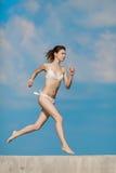 运行白色的比基尼泳装的赤足亭亭玉立的女孩户外 免版税库存图片