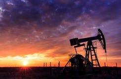 运行的油和煤气井和日落天空 库存照片