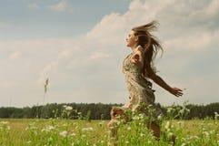 运行草甸的女孩 图库摄影
