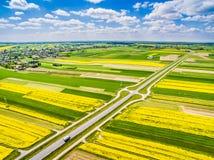 运行通过五颜六色的领域的路 农村风景有鸟` s眼睛视图 免版税图库摄影