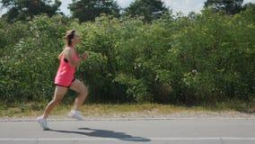 运行通过公园的桃红色衬衣的可爱的年轻深色的女孩 做锻炼的嬉戏妇女 耳机的训练的女孩  影视素材