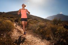 运行通过山风景的白肤金发的母足迹赛跑者 免版税库存照片
