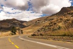 运行通过干燥橙色冬天山Landsca的柏油路 免版税图库摄影
