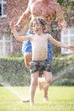 运行通过庭院喷水隆头的父亲和儿子 图库摄影