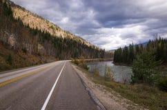 运行通过树木丛生的山的涂焦油高速公路 免版税库存图片