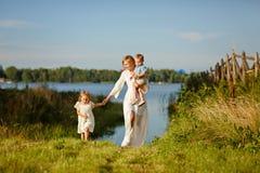 运行通过草的一件白色礼服的妈妈,握手 免版税图库摄影