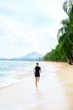 运行 跑在海滩的适合的运动人 执行 健康寿命 免版税库存照片