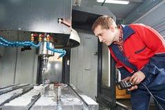 运行CNC机械中心的工作者 免版税库存照片