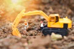 运转与反向铲挖掘机的建筑工人小雕象开掘的地面土壤 图库摄影