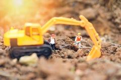 运转与反向铲挖掘机的建筑工人小雕象开掘的地面土壤 免版税库存图片