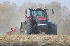 运转在一块麦地的拖拉机在捷克共和国 免版税图库摄影