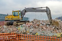运转在一排老工厂厂房的爆破的挖掘机 库存图片