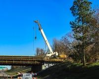 运转在一条高速公路上的桥梁的大白色移动式起重机有车道的由高杉树关闭了 免版税图库摄影