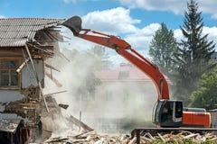 运转在一老住宅buildi的爆破的挖掘机 免版税库存照片