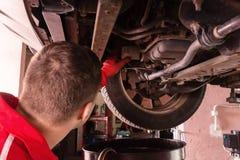 运转在一辆被举的汽车下的制服的汽车修理师 库存照片