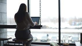 运转在与膝上型计算机的咖啡馆的一件白色衬衣的确信的可爱的妇女 影视素材