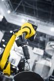 运转在产业环境里的自动机器人胳膊 免版税库存照片