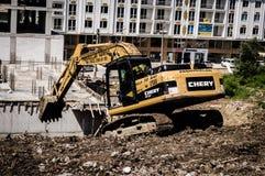 运转在倾斜的土地的挖掘机 免版税库存图片