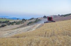 运转在倾斜的地面,西班牙的联合收割机 免版税库存照片