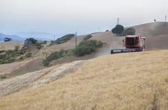 运转在倾斜的地面,西班牙的联合收割机 图库摄影
