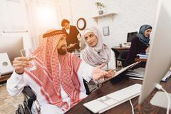 运转在办公室的轮椅的残疾阿拉伯人 人采取与女性工友的笔记 库存图片