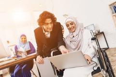 运转在办公室的轮椅的残疾阿拉伯妇女 妇女与男性工友谈话 免版税图库摄影