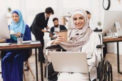 运转在办公室的轮椅的残疾阿拉伯妇女 妇女在膝上型计算机和饮用的咖啡工作 库存图片
