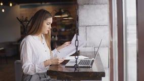运转在咖啡馆的一台膝上型计算机的一件白色衬衣的美丽的女实业家 股票视频