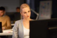 运转在夜办公室的计算机的女实业家 免版税库存照片