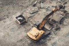 运转在小山的灌溉水坝的顶视图黄色工业推土机挖掘机反向铲在建造场所 免版税图库摄影