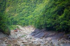 运转在小河床上的挖掘机 库存照片