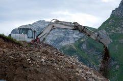 运转在山的挖掘机 免版税库存图片